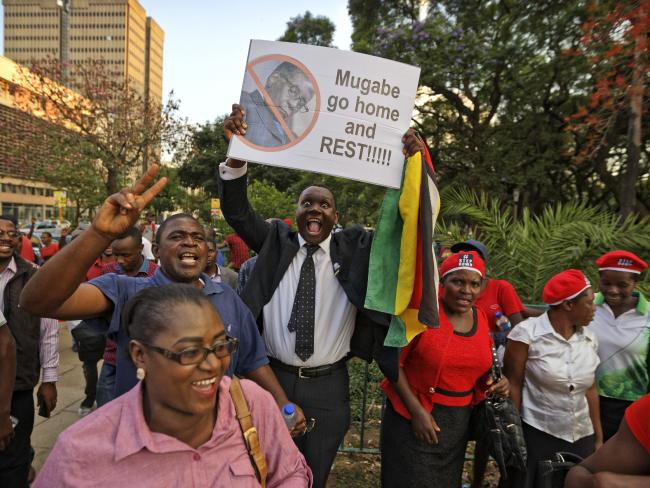 Zimbabweans celebrate outside the parliament building immediately after hearing the news that President Robert Mugabe had resigned, in downtown Harare. Picture: AP Photo/Ben Curtis