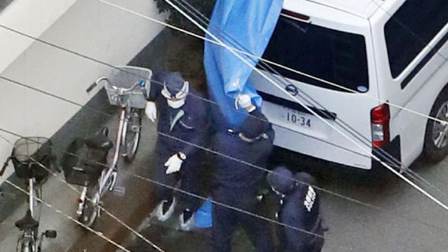 Police investigators outside an apartment where the dead infants were kept. Picture: AP