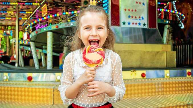 generic fair, cute little girl with lollipop at amusement park