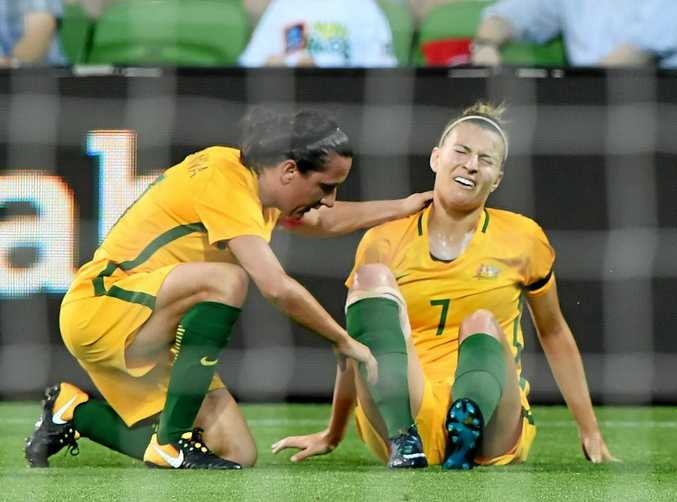 Steph Catley grimaces after being trampled on in Australia's clash against China in Melbourne.