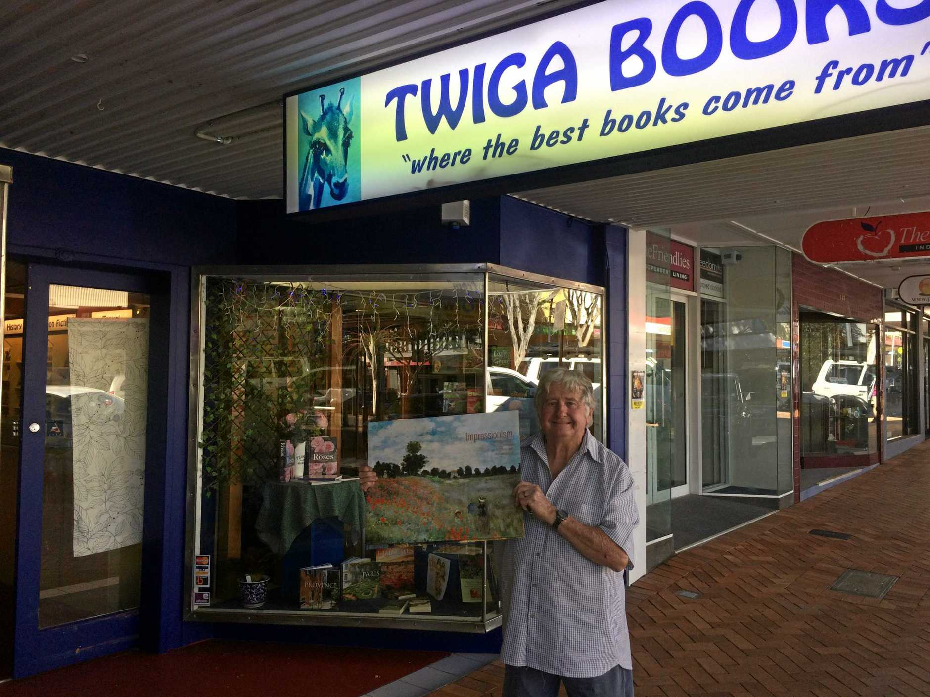 STANDING TALL: Roger Broadley presents Gympie's new book store in Mary Street, possibly the only one in the world named after a giraffe.