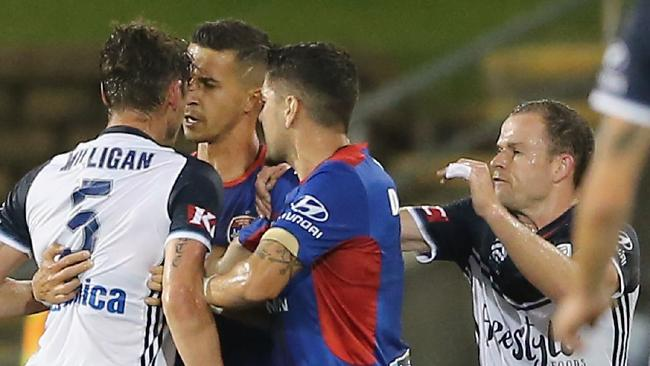 Melbourne Victory's Mark Milligan lunges at Newcastle's Daniel Georgevski and is sent off.