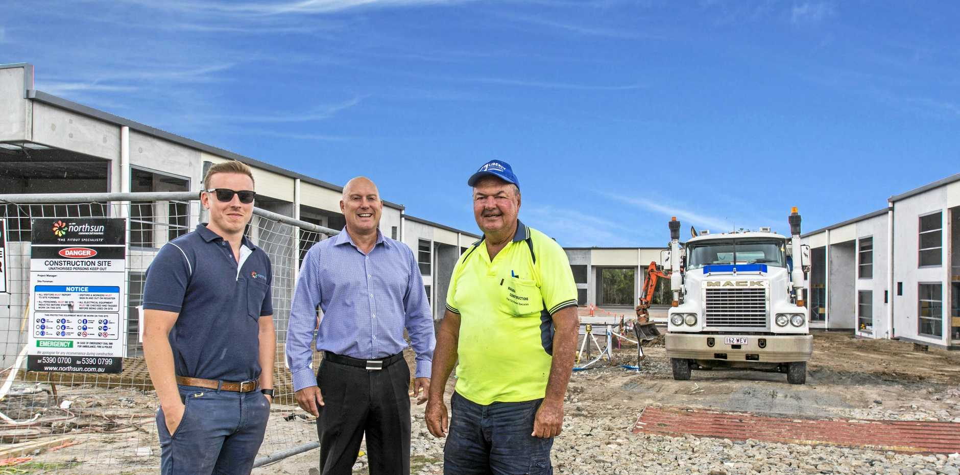 WIDE APPEAL: Jack Williams, left, with Rob Makara, right, and Glen Grimish of CBRE at Equinox Place, Bells Creek.