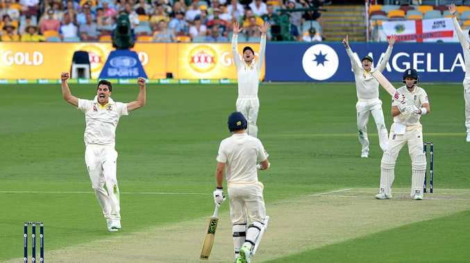 Pat Cummins (left) celebrates after trapping England captain Joe Root leg before wicket on day one of the first Ashes Test in Brisbane.