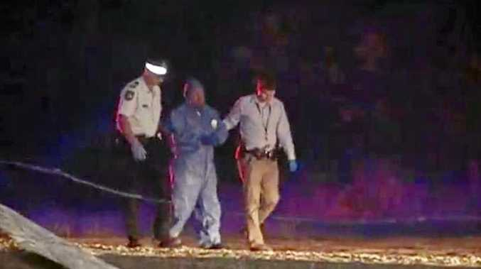 INVESTIGATION: Bundaberg police escort a man from the scene of a stabbing at Yandaran.