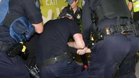 The young Schoolie pulled from the dance party is arrested by police. Picture Mike Batterham