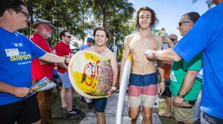 Surfers Liam Egan and Dave Lauchs work their way through a sea of Party volunteers to vote in the State of Election after enjoying most of the day in the water at Alexandra Headland. Picture: Lachie Millard