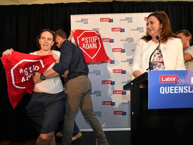 Anti-Adani coal mine protesters invade the stage as Queensland Premier Annastacia Palaszczuk (right) speaks on the campaign's first day.