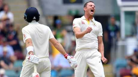 Australian paceman Josh Hazlewood celebrates taking the wicket of England captain Joe Root (left) at the Gabba on Sunday.