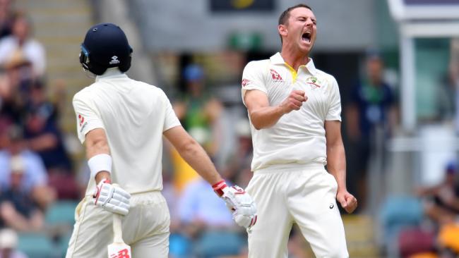 Australian paceman Josh Hazlewood celebrates taking the wicket of England captain Joe Root (left) at the Gabba on Sunday.
