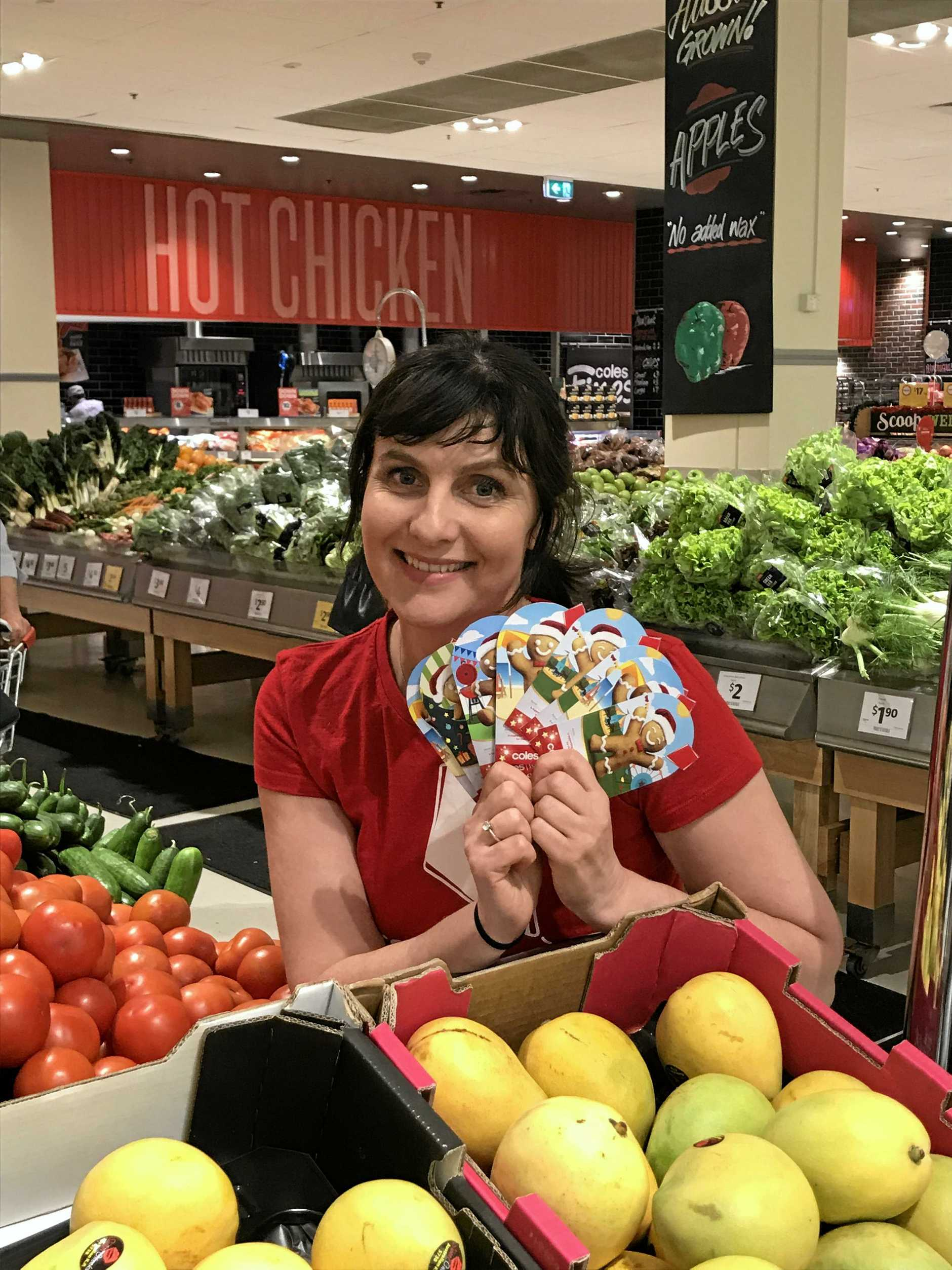 Redkite's Isobel Lindley with donation cards for this month's Christmas appeal at Coles.