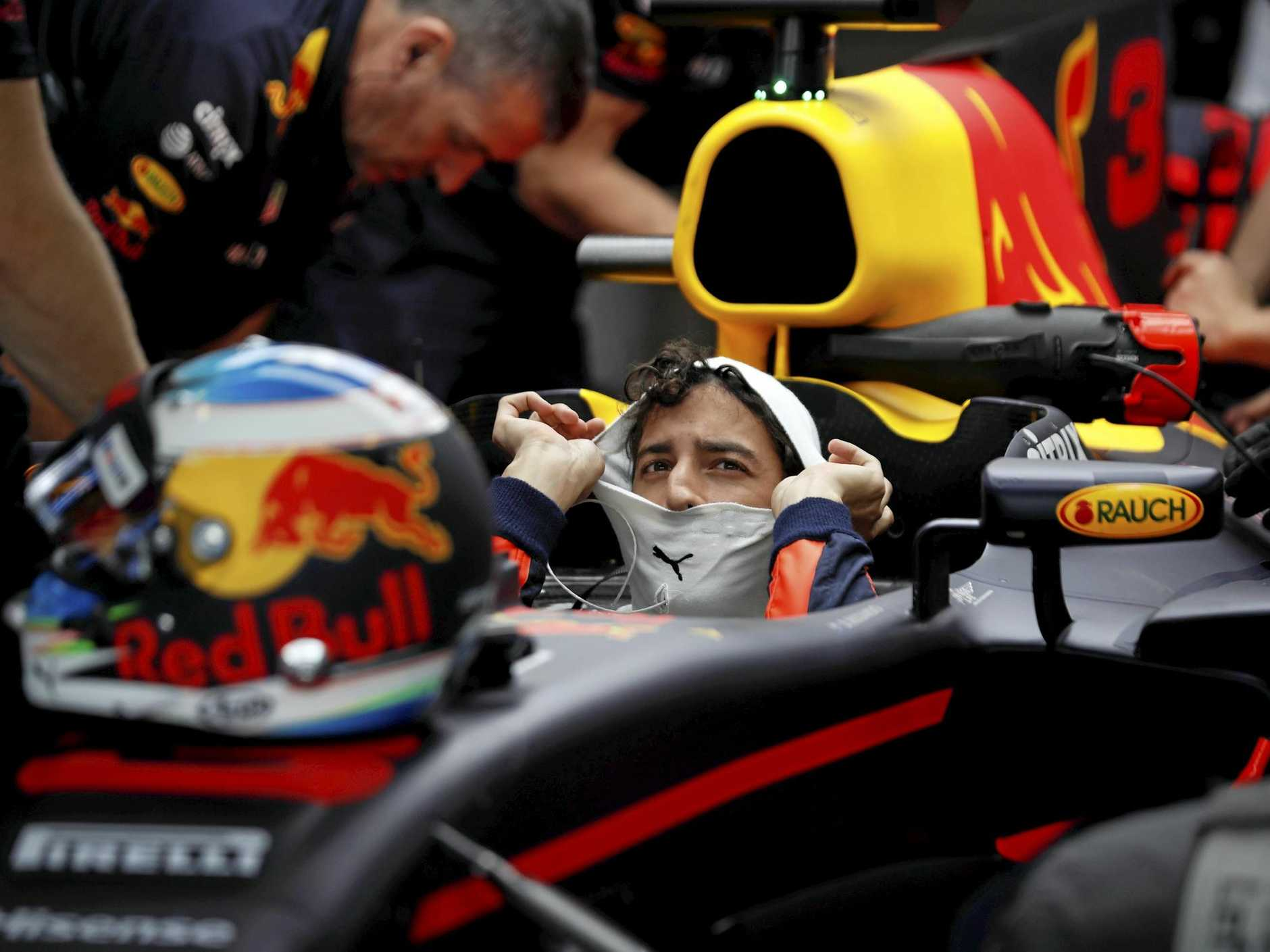 Red Bull driver Daniel Ricciardo of Australia sits in his car.