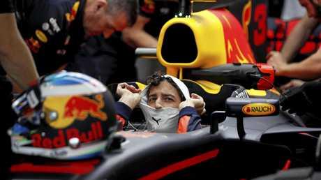 Red Bull driver Daniel Ricciardo of Australia sits in his car.