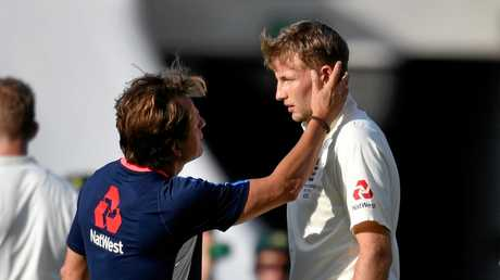 Joe Root (right) of England is examined by medical staff after being hit by a bouncer bowled by Mitchell Starc.