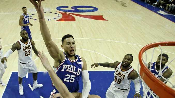 Philadelphia 76ers' Ben Simmons (25) goes up for a shot against the Cavaliers.