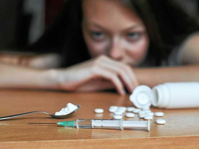 Junkie girl looking at drugs