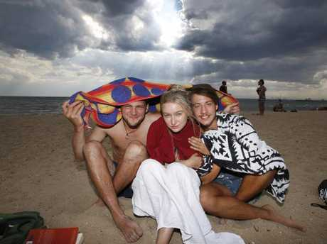 Jonas Kanis, Lotta Jahnke and Thomas Horn take shelter as a cool change hits St Kilda Beach. Picture: David Caird