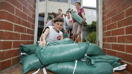 Felix Ridley-Whittle sandbags the front gate of Royal Brighton Yacht Club. Picture: David Caird