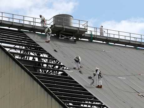Workers wearing asbestos safety equipment remove roof sheeting from large sugar cane sheds in Cairns. Picture: Justin Brierty