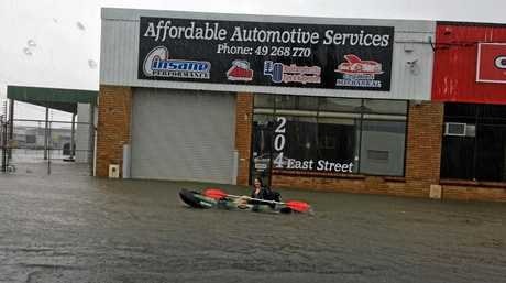 A woman in a kayak paddles down a Rocky street after the region was drenched with rain on Sunday.