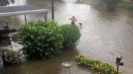 A man is seen with a rake in the floodwaters on Wackford St in Park Avenue.