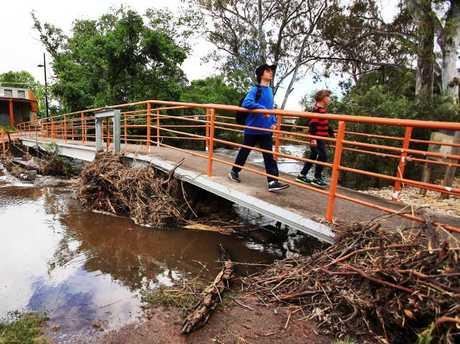 Children cross a footbridge clogged with flood debris in Euroa. Picture: Aaron Francis/The Australian