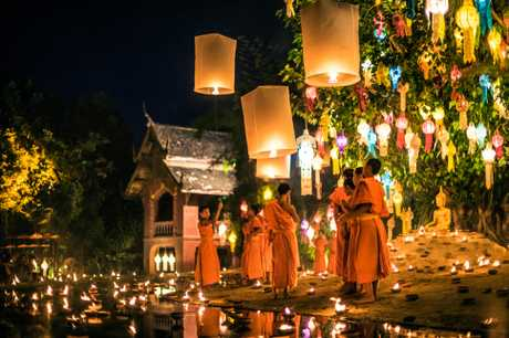Traditional monk lights floating balloon made of paper annually at Wat Phan Tao temple during the Loi Krathong Festival in Chiang Mai.