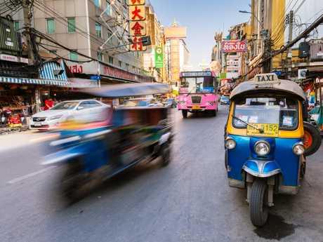 A tuk-tuk taxi parked near a street market in Bangkok, Thailand.