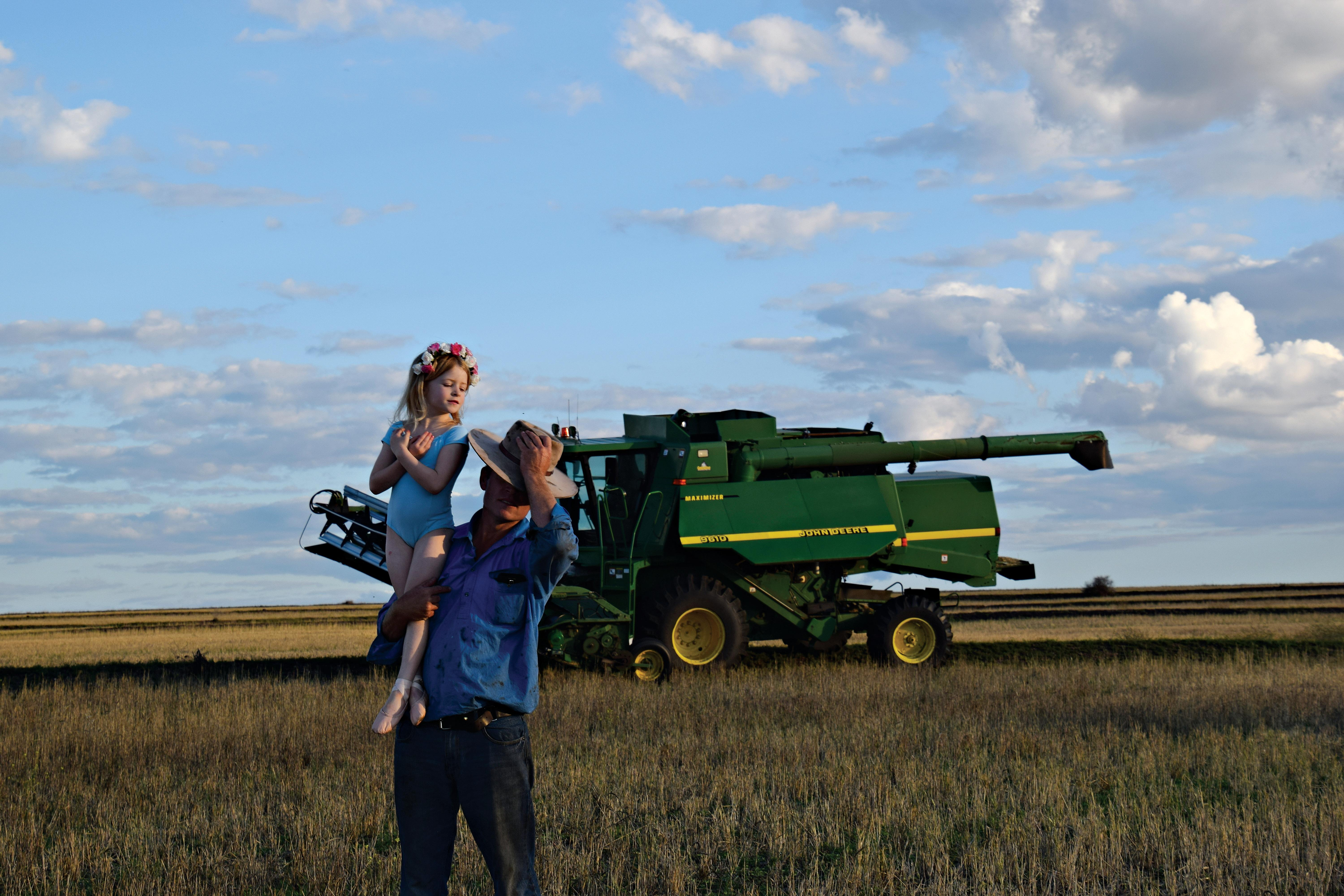 Florence Nason, 5, sits on dad Patrick Nason's shoulders while he takes a break from harvesting on their farm in western Queensland.