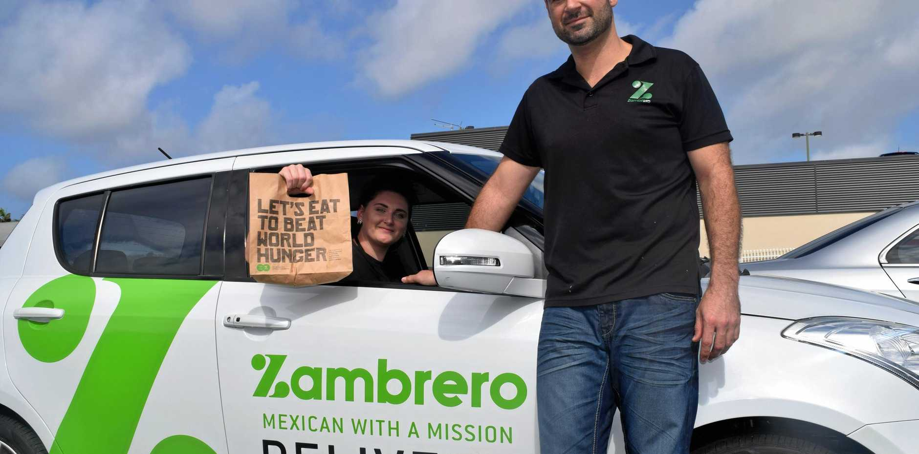 Zambrero employee Emma Crocker on the way to a delivery with franchise partner Peter Quinn.