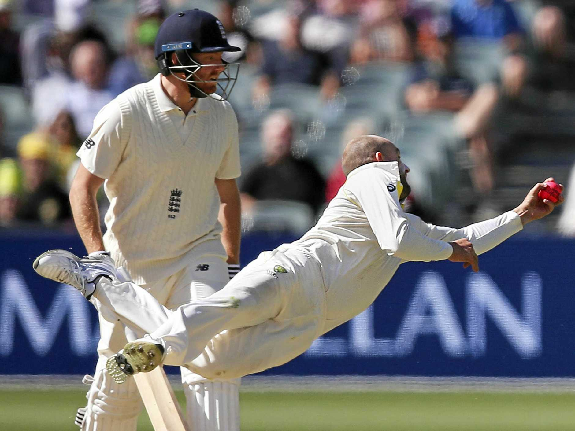 Nathan Lyon dives to his left to take a catch off his own bowling to dismiss England's Moeen Ali.