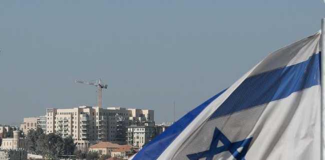 The Israeli flag flutters.