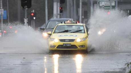 Cars pass through the water covered intersection of Racecourse and Flemington Rd in Melbourne. Picture: James Ross.