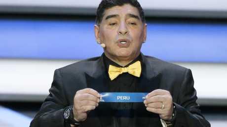 Argentine soccer legend Diego Maradona holds up the team name of Peru