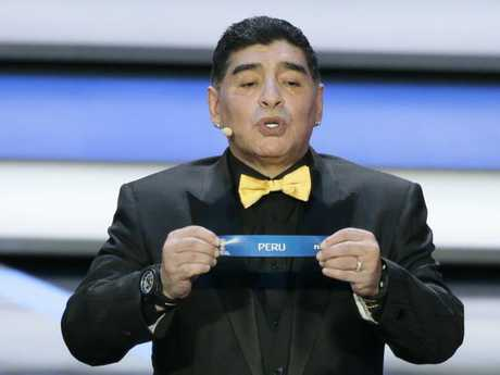 Argentine soccer legend Diego Maradona holds up the team name of Peru