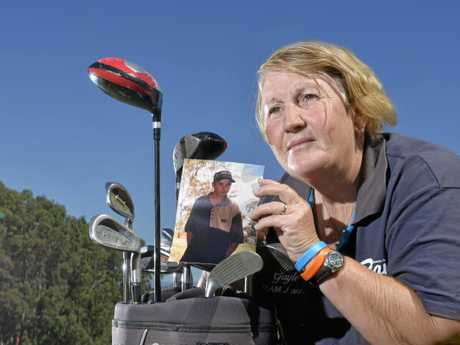 Gayle Daetz holds a picture of her son Jody at a charity golf day she hosted.