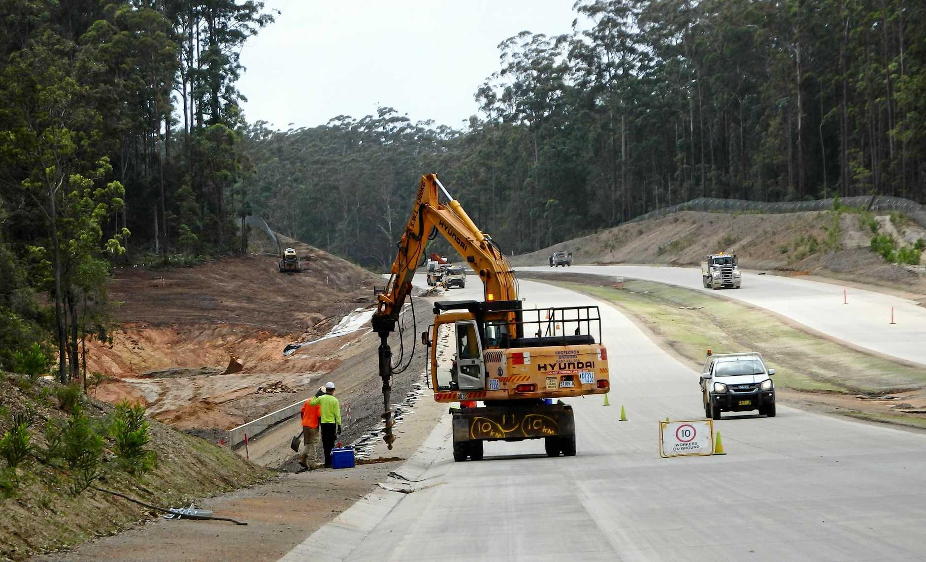 Work crews drilling holes for support posts for wire ropes on the new highway edges.