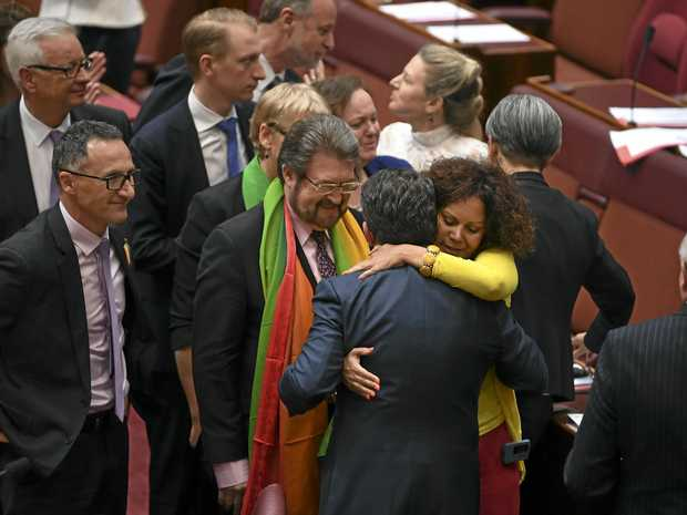 Coalition Senator Dean Smith receives a hug from Labor Senator Malarndirri McCarthy after the same-sex marriage bill passed the Senate in the Senate chamber at Parliament House in Canberra, Wednesday, November 29, 2017.