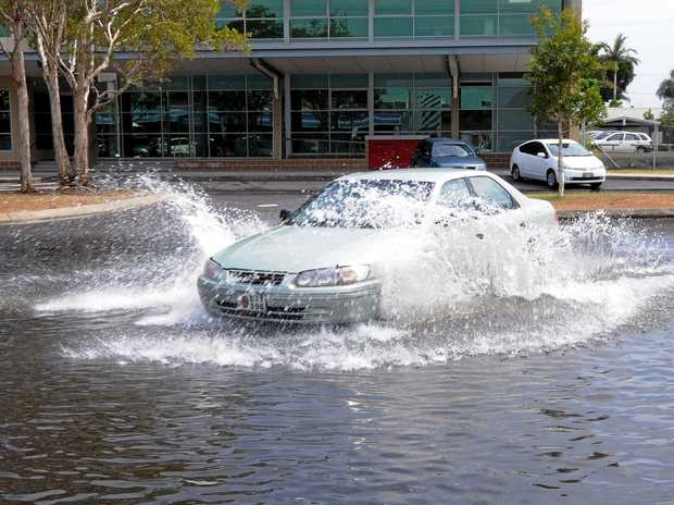 File photo of a car driving through king tide floodwaters in Ballina.