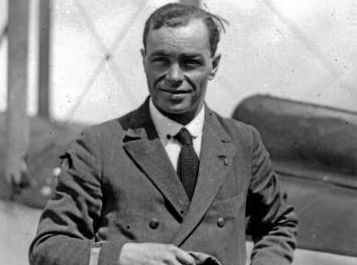 Portrait of Bert Hinkler, pioneer Australian aviator, standing beside a plane and carrying flying cap and goggles.