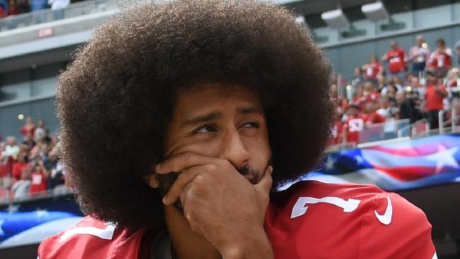 Colin Kaepernick, formerly of the San Francisco 49ers, kneels in protest on the sideline during the playing of the national anthem. Picture: Getty Images