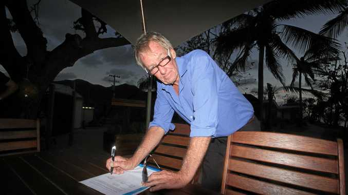Owner of the Tatemaya Maru Patrick Von Stieglitz signs the petition to rid the Whitsundays of the Tateyama Maru in April this year.