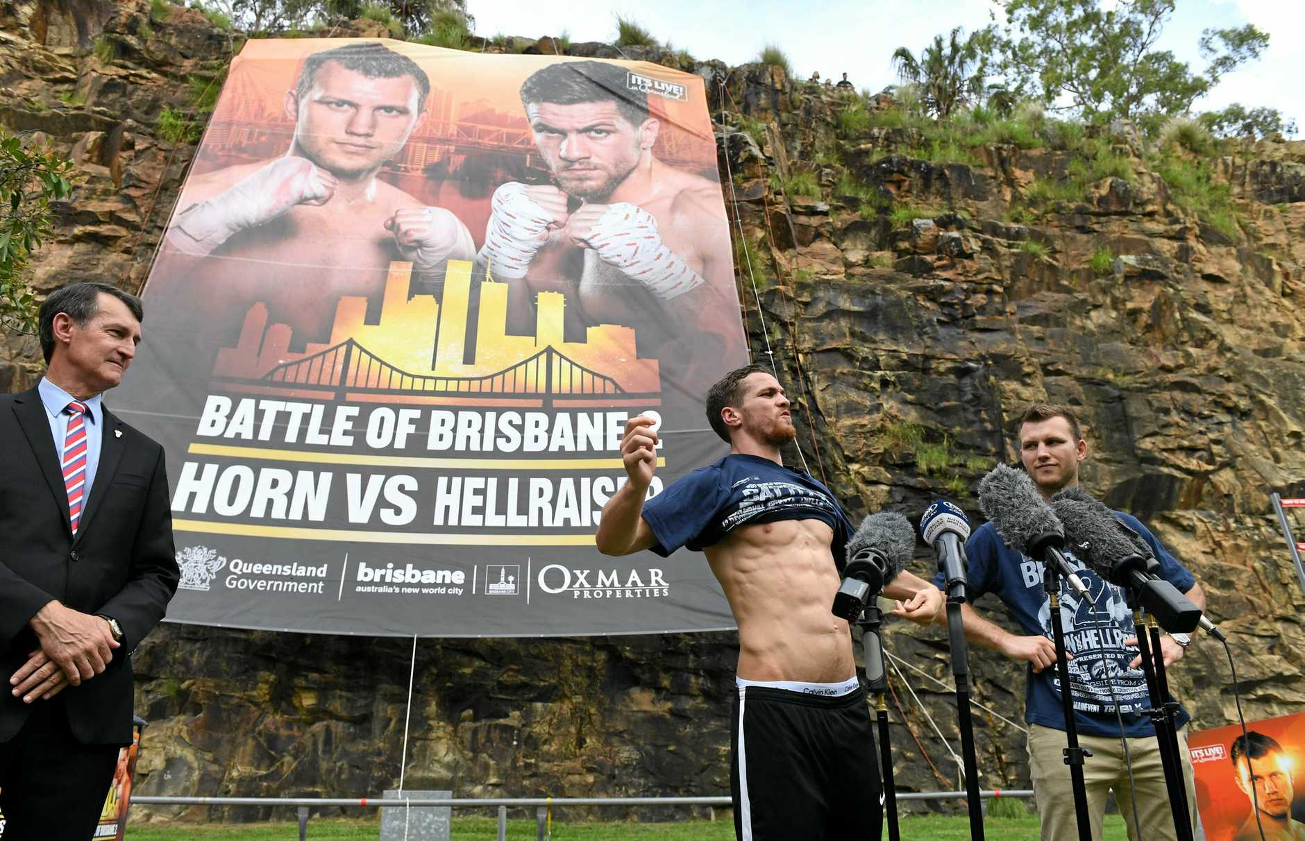 British boxer Gary Corcoran (centre), watched by Brisbane Lord Mayor Graham Quirk (left) and Australian boxer and WBO world welterweight champion Jeff Horn, shows his physique to the request of promoter Dean Lonergan during a media event in Brisbane, Tuesday, December 5, 2017. Horn and Corcoran will clash in a title fight dubbed