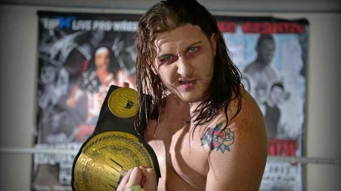 CROWD FAVOURITE: Elliott Stacey, aka Thirteen, pictured with his championship belt, is training others in the art of wrestling at the Kunda Park studio.