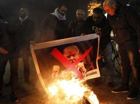 Palestinian protesters burn pictures of US President Donald Trump at the manger square in Bethlehem. Picture: AFP/Musa Al Shaer