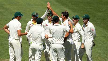 Australian players celebrate with Mitchell Starc after he claimed the wicket of England's Craig Overton.
