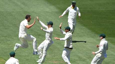 Australian bowler Josh Hazlewood (left) celebrates with captain with Steve Smith after dismissing England captain Joe Root.