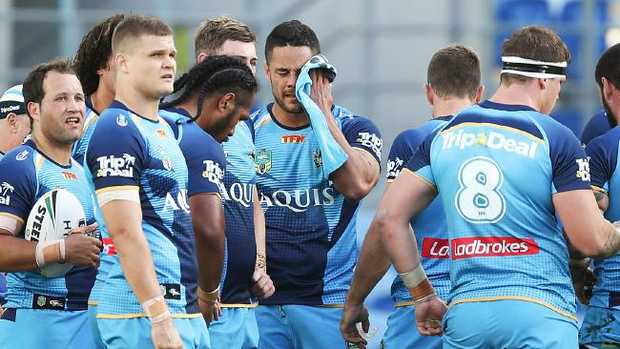Jarryd Hayne wipes his face as the rest of the team look on.