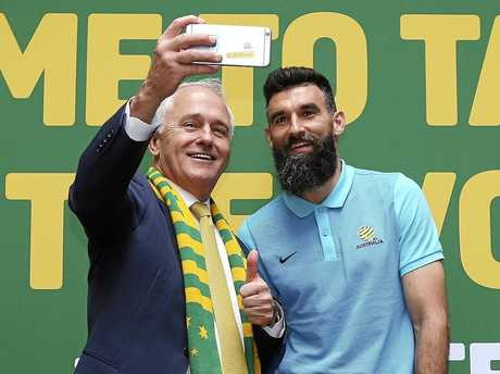 Australian Prime Minister Malcolm Turnbull, left, takes a selfie photo with Australian soccer team captain Mile Jedinak during a reception following their qualification to the 2018 soccer World Cup in Sydney, Australia, Thursday, Nov. 16, 2017. Australia's 3-1 victory over Honduras secured the next-to-last spot in the World Cup in Russia. (AP Photo/Rick Rycroft)