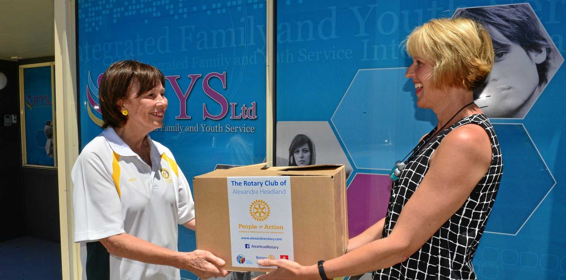 Alexandra Headland Rotary member Prue Byrnes donates one of 200 hampers to foster carer Julie Stringer that will help support all foster carers on the Coast.